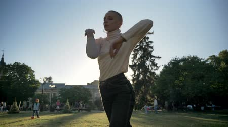 Young extraordinary bold girl ballerina is dancing on grass in park in daylight in summer, watching at camera, movement concept, bottom view