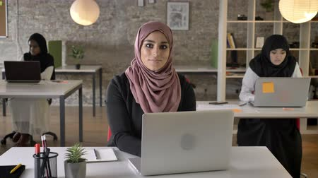 libya : Three young muslim womans in hijab sitting and working in modern office, muslim beautiful woman looking in camera and smiling Stock Footage