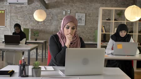 arabesco : Three young muslim womans in hijab sitting and typing on laptop in modern office, muslim woman coughing and working Vídeos