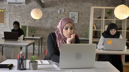 feminism : Three young muslim womans in hijab sitting and typing on laptop in modern office, muslim woman yawning and working, tired Stock Footage