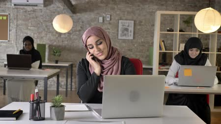 libya : Three young muslim womans in hijab sitting and working in modern office, beautiful muslim woman talking on phone, smiling