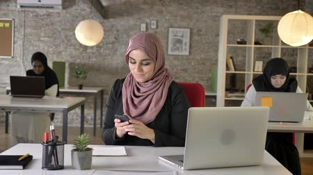 feminism : Three young muslim womans in hijab sitting and working in modern office, pretty female worker typing on phone