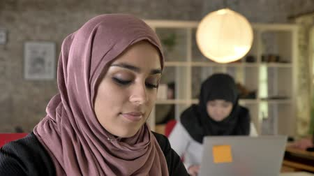 feminism : Portrait of young muslim women in hijab working, thinking, two womens sitting and typing on laptop in modern office