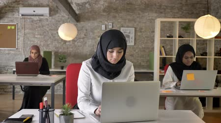 libya : Three young muslim womens in hijab sitting and working in modern office, pretty female worker typing on laptop, concentrated