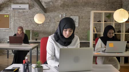 libya : Three young muslim womens in hijab sitting and working in modern office, islamic female worker typing on laptop, smiling at camera