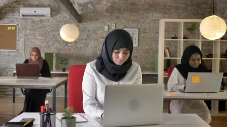 libya : Three young muslim womens in hijab working in modern office, beautiful female worker typing on laptop, smiling at camera, happy