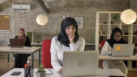 ближневосточный : Three young muslim womens in hijab sitting and typing on laptop in modern office, sick woman coughing and working