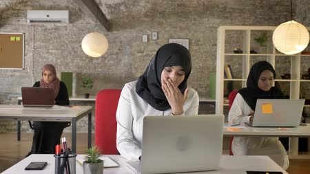 libya : Three young muslim womens in hijab sitting and working on laptop in modern office, muslim woman yawning, tired Stock Footage