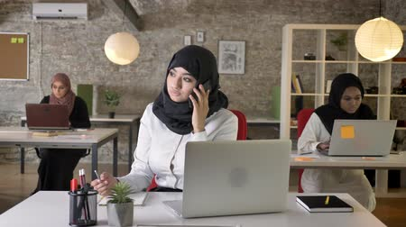libya : Three young muslim womens in hijab sitting and typing on laptop in modern office, beautiful muslim woman talking on phone, busy
