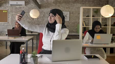 kelet : Three young muslim womens in hijab working in modern office, while other muslim woman take selfie with smartphone Stock mozgókép