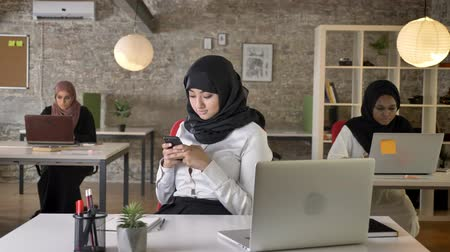 libya : Three young muslim womens in hijab sitting and typing on laptop in modern office, charming female worker texting on phone