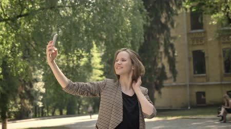 bob hairstyle : Young attractive girl is making selfie in park in daytime, in summer, communication concept