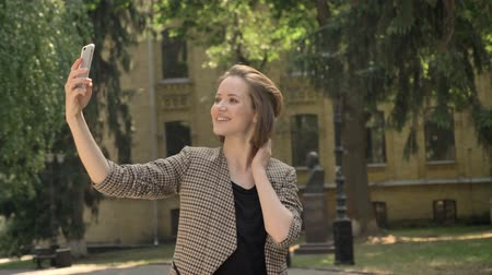 expressar : Young attractive girl is making selfie in park in daytime, in summer, touching hair, communication concept