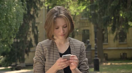 bob hairstyle : Young attractive concentrated girl is typing message on smartphone in park in daytime, in summer, communication concept Stock Footage