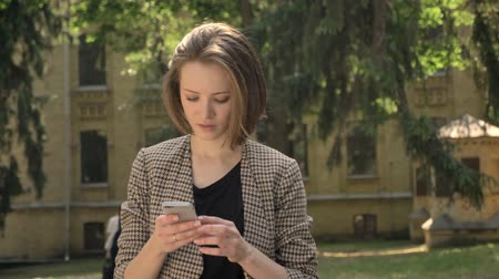 bob hairstyle : Young attractive concentrated girl is typing message on smartphone in park in daytime, in summer, watching at camera, communication concept