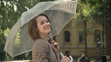 bob hairstyle : Young attractive girl is walking in park with umbrella in daytime, in summer, smiling, watching at camera