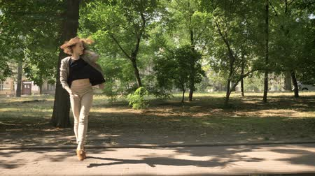 felvonás : Young beautiful girl is dancing on path in park in daytime, in summer, movement concept, side view, dolly shot