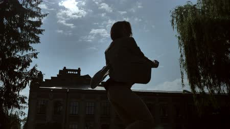 felvonás : Silhouette of young unknown girl is dancing in shadow in daytime, in summer, movement concept, bottom view, dolly shot