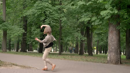 bob hairstyle : Young pretty girl dancer is dancing in park in daytime, in summer, movement concept, side view, dolly shot Stock Footage
