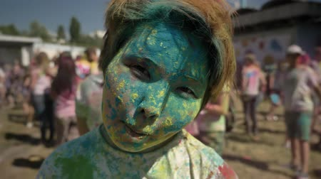 eleven : Young happy asian girl is smiling and winking with colourful powder on holi festival in daytime in summer, color concept, flirt concept Stock mozgókép