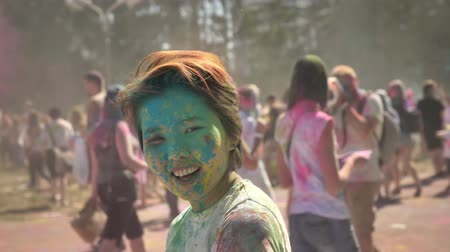 truly : Young happy asian girl is smiling with colourful powder on holi festival in daytime in summer, color concept, flirt concept Stock Footage