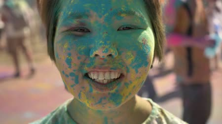 truly : Face of young happy asian girl is smiling with colourful powder on holi festival in daytime in summer, color concept, emotional concept