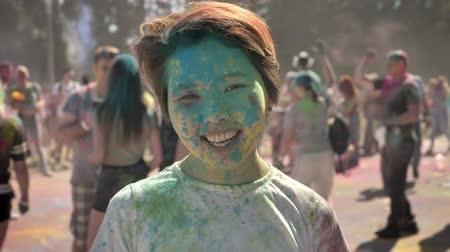 truly : Young happy asian girl is smiling with colourful powder on holi festival in daytime in summer, watching at camera, color concept