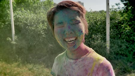 фест : Young cheerfyl asian girl in colors is thrown with colourful powder on holi festival in daytime in summer, color concept Стоковые видеозаписи