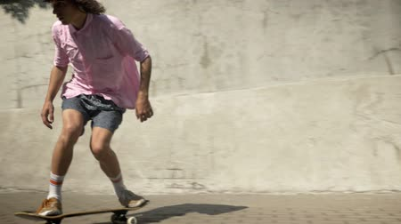 longboarding : Skateboarder doing skateboard trick on old wall and skating in modern city