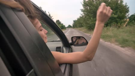 álmodozó : Young beautiful girl dreamer puts head and hand out of car window during ride, trevel concept, dreaming concept