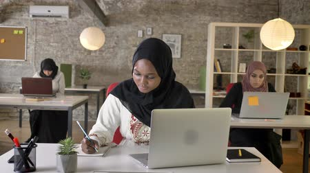 beatiful : Black young muslim woman in hijab typing on laptop and writing on paper, three beautiful muslim womens working in office Stock Footage