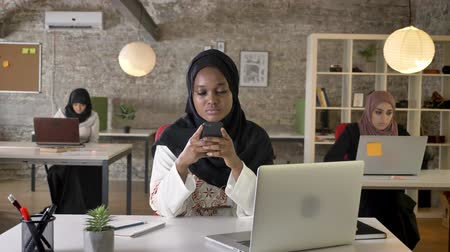 beatiful : Young black muslim women in hijab texting on phone and looking in camera, three beautiful muslim womens sitting in modern office