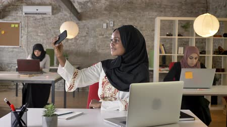 beatiful : Young black muslim women in hijab taking selfie in modern office, three beautiful muslim womens sitting and working on laptop Stock Footage