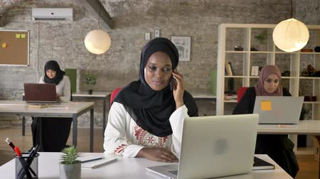 beatiful : Young black muslim women in hijab talking on phone in modern office, three pretty muslim womens sitting and working on laptop
