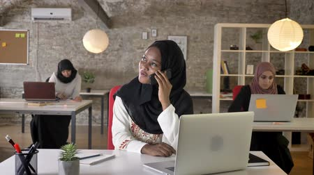 beatiful : Young black muslim women in hijab talking on phone, smiling and laughing in office, three pretty muslim womens working on laptop