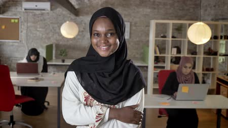 beatiful : Young black muslim women in hijab looking in camera, smiling, three womens working on laptop in modern office in background Stock Footage