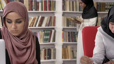 vállkendő : Three young muslim womens in hijab studying in library, reading and writing, shelves with books background, islamic students