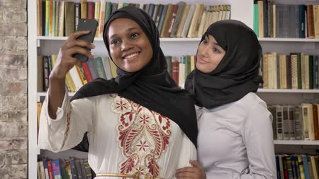 akadémia : Young black muslim women in hijab with white friend taking selfie in library, smiling and happy, islamic students