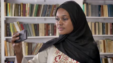 akadémia : Young black muslim women in hijab taking selfie then looking at phone in library, smiling, african muslim student Stock mozgókép