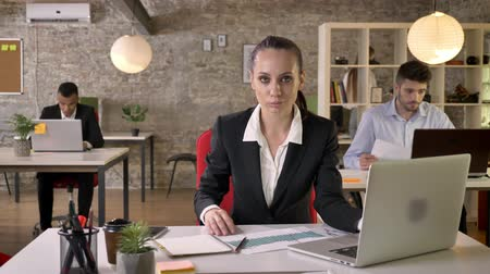 expressar : Young beautiful business woman is watching laptop in office, watching at camera, smiling, people are networking with technologies, working concept, business concept, communication concept, emotional concept