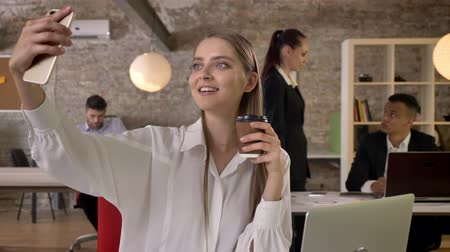 make photo : Young attractive businesswoman is making selfie with coffee on smartphone in office, her colleagues are networking with technologies, working concept, business concept, communication concept Stock Footage