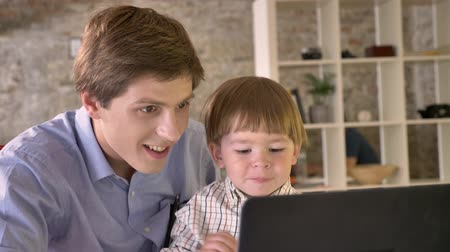 főnök : Young father holding his smiling son and looking at laptop, sitting in modern office, happy