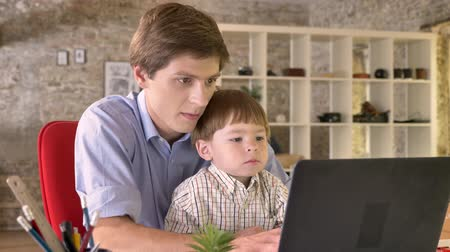родственники : Young father holding his little son and working on laptop, busy, sitting in modern office Стоковые видеозаписи