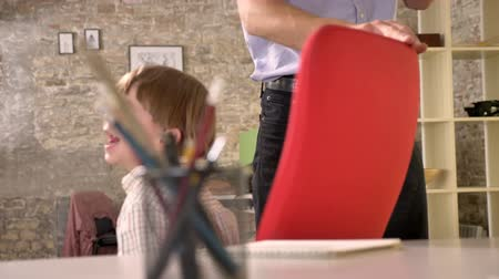 kin : Father circling around his little son on chair, happy kid cheering and sitting in modern office