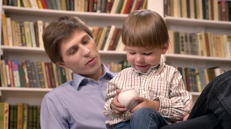 родственники : Little boy sitting with his young father and holding ball, shelves with books background Стоковые видеозаписи