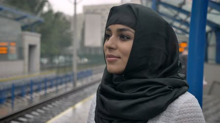 locomotiva : Young dreaming muslim woman in hijab is waiting for train, religion concept, urban concept Vídeos