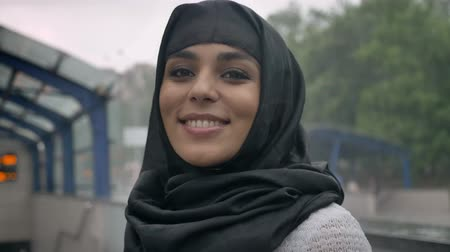 pesadelo : Young dreaming muslim woman in hijab is smiling on railway station, religion concept, urban concept