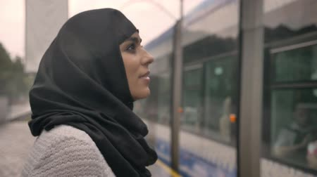 платформа : Young muslim woman in hijab is watching how train is coming under raining, religion concept, transport concept, weather concept Стоковые видеозаписи