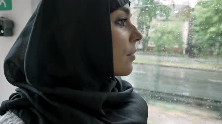 pesadelo : Young muslim woman in hijab is watching in window in trolleybus, rainy weather.