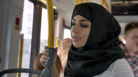 álmodozó : Young muslim woman in hijab is riding in bus, transport concept, urban concept, dreaming concept, side view Stock mozgókép